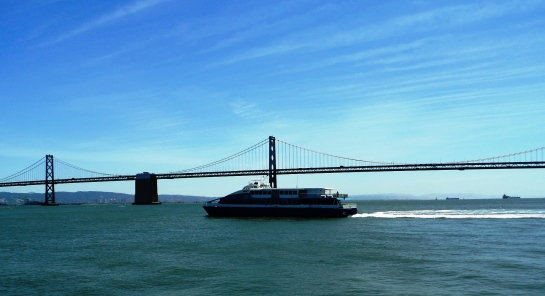 A ship passes by the Bay Bridge, San Francisco, CA